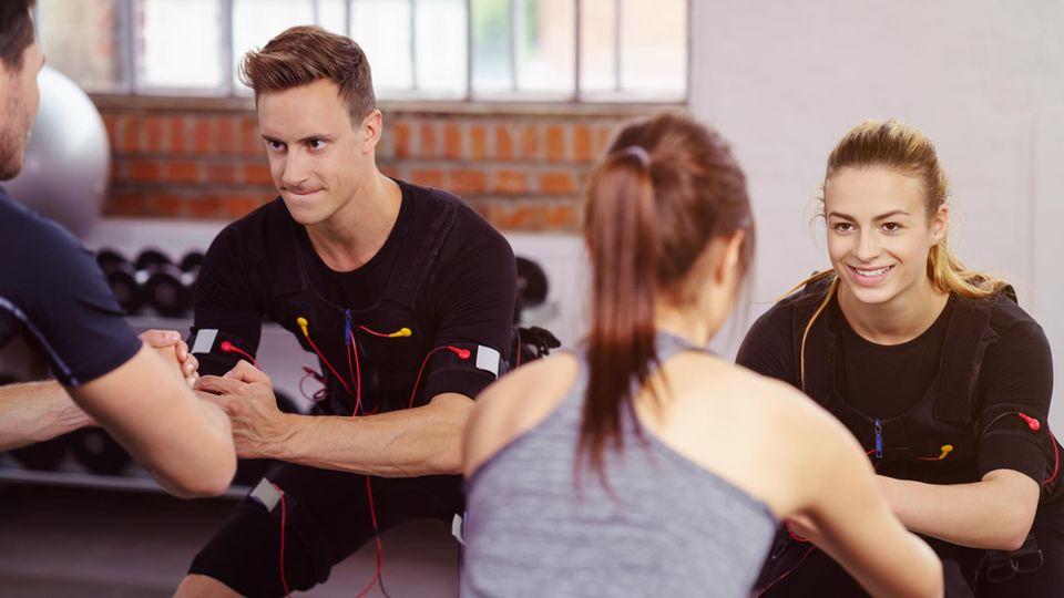 EMS-Training: Vier Sportler beim Power-Work-out mit Strom