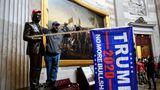 Ein Demonstrant skandiertim Inneren des US-Kapitols und setzt einer Statue eine Trump-Mütze auf