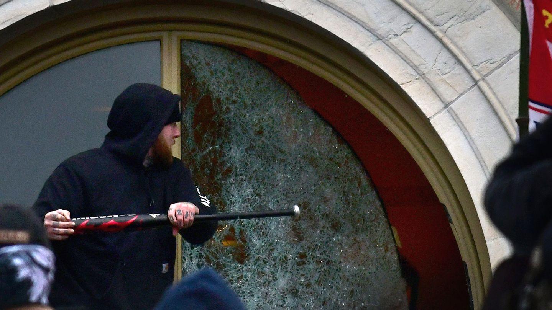 Ein AnhängerTrumps zerschlägt ein Fenster des US-Kapitolgebäudes