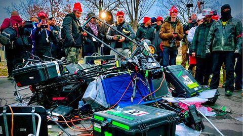 Trump-Anhänger stehen vor einem Haufen zerstörtenEquipments internationaler Medienvertreter