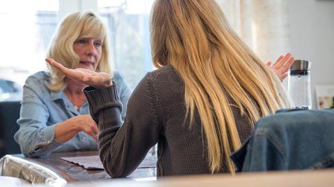 Zwei blonde Frauen diskutieren am Tisch