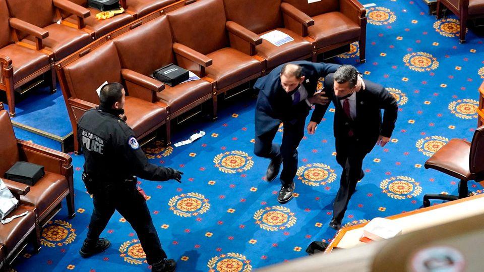 Ein Abgeordneter wird von Sicherheitskräften aus dem Saal gebracht
