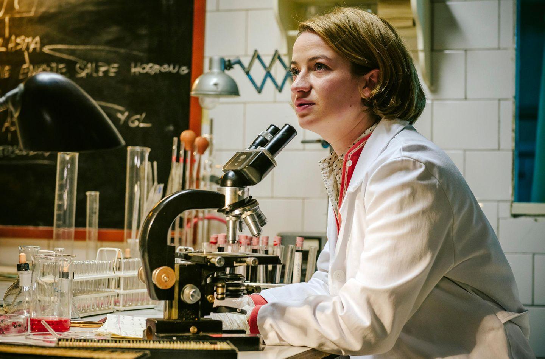 """Sie ist die Hauptfigur der dritten Staffel von """"Charité"""":Dr. Ella Wendt (Nina Gummich). Die junge Ärztin ist eigentlich an das berühmte Krankenhaus gekommen, weil sie dort ihre Forschungen zur Krebsfrüherkennung voranbringen will. Doch dazu hat sie kaum Zeit: Die Charité ist chronisch unterbesetzt, immer mehr Mediziner verlassen die DDR in Richtung Westen."""