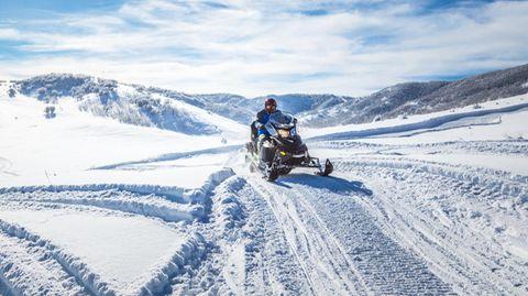 Eine Person auf einem Motorschlitten in verschneiter Landschaft
