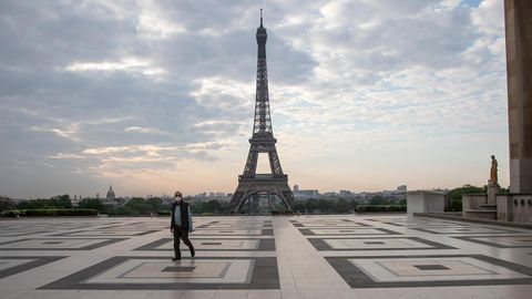 Frankreich, Paris: Ein Passant auf dem Trocadero-Platz mit Blick auf den Eiffelturm trägt einen Mundschutz