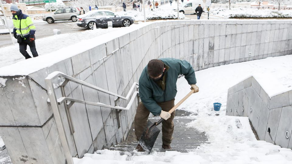 Ein Mann in dunkelgrüner Jacke und brauner Hose schaufelt Schnee von den Stufen einer steinernen Treppe