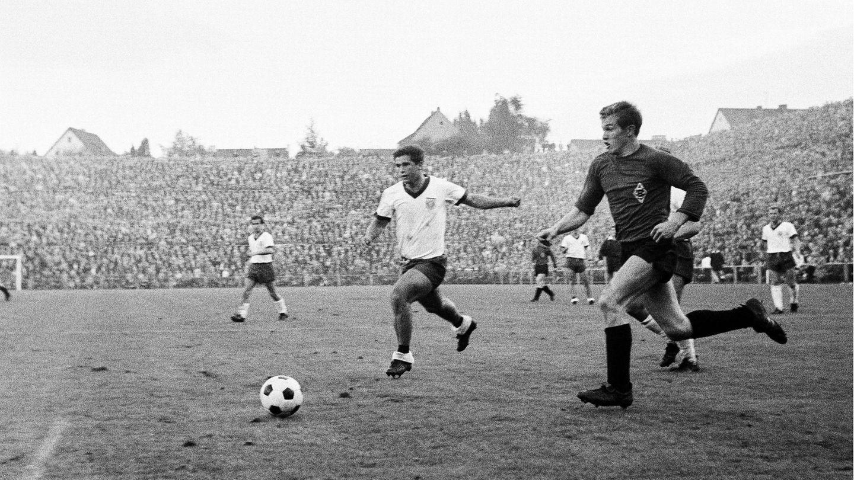 2. Oktober 1965  Das erste Duell der beiden Klubs in der Bundesliga, beide sindfrisch aufgestiegen und treffen am Bökelbergaufeinander. Einige Namen sindnoch sehr gegenwärtig. Jupp Heynckes (vorne links) zum Beispiel, damals 20 Jahre alt, liefert sich ein Laufduell mit Gerd Müller, zu diesem Zeitpunkt 19. Beide sollten ihre Teamsbis weit in die Siebziger prägen. Günter Netzer schießt übrigens das 1:0 für Gladbach, dann drehen die Tore von Werner Olk und Gerd Müller die Partie zu Gunsten der Bayern.