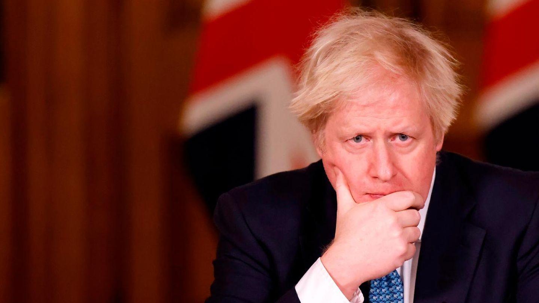Hinter einem Rednerpult steht Boris Johnson und stützt seinen Kopf sorgenvoll auf eine Hand