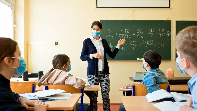 Eine Schulklasse und die Lehrerin mit Mund-Nase-Schutzmasken