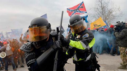 Zwei Bewaffnete Männer in Polizei-Schutzkleidung und Helmen drehen sich von der Menge der Trump-Unterstützer weg