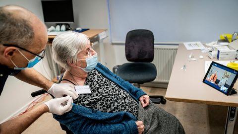 Eine ältere Frau wird von einem Arzt gegen Corona geimpft
