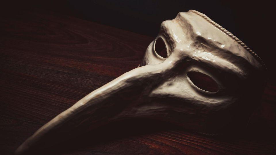 Eine venezianische Pestmaske auf einem Tisch