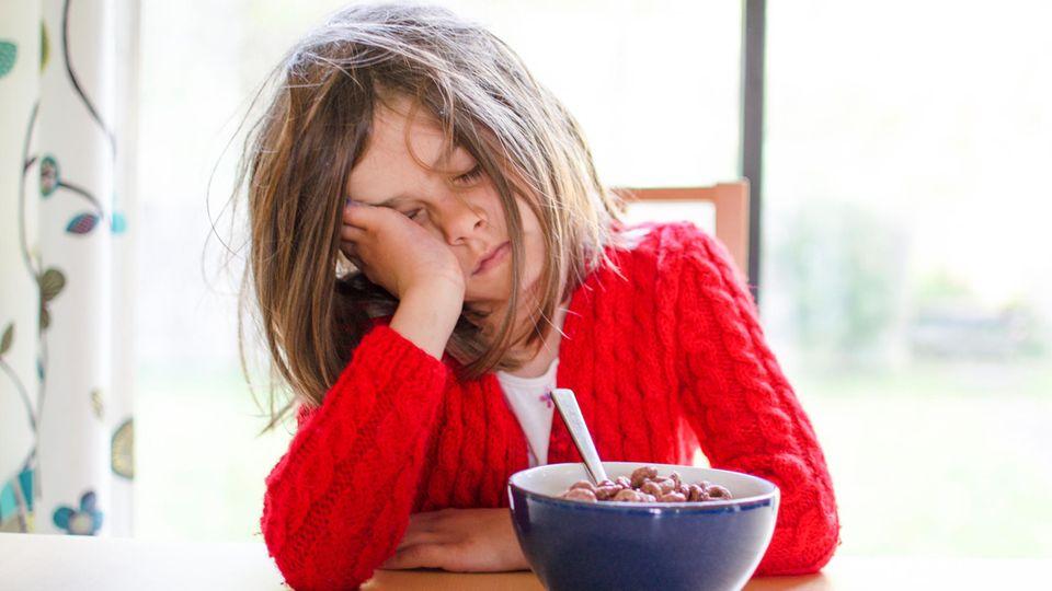 Ein Mädchen sitzt müde am Frühstückstisch