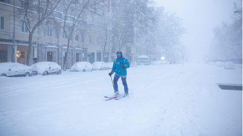Ein Mann ist mit Skiern auf einer verschneiten Straße in Madrid unterwegs