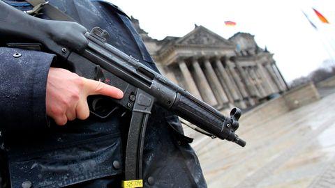 Ein bewaffneter Polizist steht vor dem Reichstagsgebäude