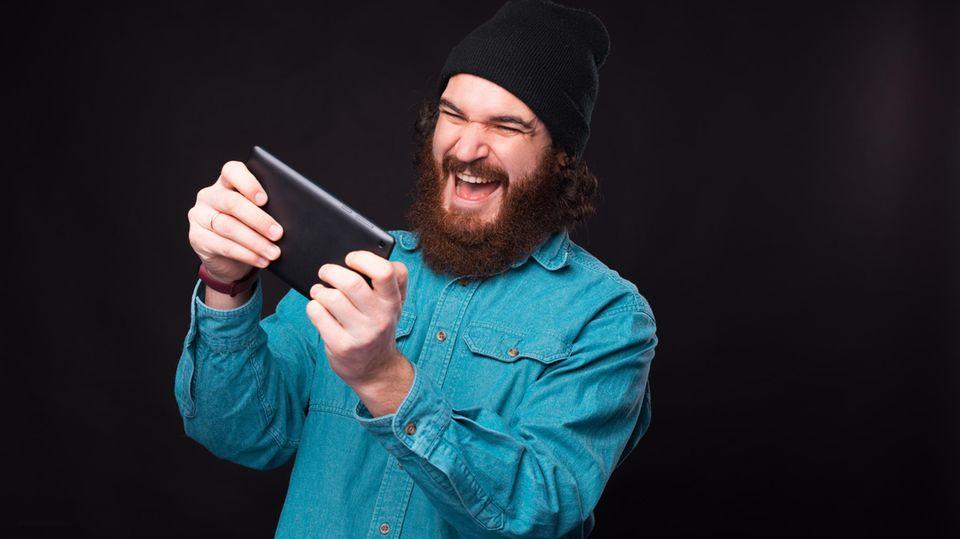 Ein Mann spielt mit seinem Gaming-Tablet. Der Mund ist weit aufgerissen, die Augen vor Freude zugekniffen.