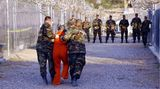 """11. Januar 2002: In den Käfigenvon Guantanamo werden erste Häftlinge eingesperrt  Das GefangenenlagerGuantanamo ist zum Sinnbild US-amerikanischer Willkür und Folter geworden.2002 hatte der damalige US-Präsident George W. Bush dasGefangenenlagerauf dem Gelände einer US-Militärbasis auf Kuba eröffnet, als Reaktion auf den Anschlag auf das World Trade Center. Am 11. Januar desselben Jahreskamen die ersten Gefangenen in dem Lager an. Die Fotoaufnahme zeigt, wiedie Militärpolizei der US-Armeeeinen Häftling in seine Zelle im Camp X-Ray bringt.  780 Häftlinge waren zunächst in dem Lager untergebracht, meist wegen angeblicher Verbindungen zum Terrornetzwerk Al-Kaida oder den Taliban. Die ersten Gefangenen waren in Käfigen im Freien eingesperrt, inzwischen besteht das Lager aus mehreren Hochsicherheitsgefängnissen.  Das Gefangenenlager wurde bereits kurz nach der Gründung weltweit kritisiert. 2013 kam eine US-Kommission offiziell zu dem Schluss,dass dort Gefangene gefoltert wurden.Amnesty Internationalforderte, das Lager aufzulösen und bezeichnete esalseinen""""Schandfleck in der Menschenrechtsbilanz der USA"""".Die zeitweise bis zu 1.000 Häftlinge wurden hier ohne Rücksicht auf Kriegs- und Völkerrecht ohne Anklage unbefristet festgesetzt und zum Teil gefoltert.  Barack Obama hatte zwarzu seinem Amtsantritt Anfang 2009 versprochen, Guantánamo innerhalb eines Jahres zu schließen, scheiterte aber damitam Widerstand der Republikaner im US-Kongress. Donald Trump wollte anschließend nichts von dem Versprechen seines Vorgängers wissen. Bis heute ist das Gefangenlager in Betrieb."""