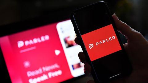 Das Logo der Internetplattform Parler auf den Bildschirmen eines Smartphones und eines Laptops
