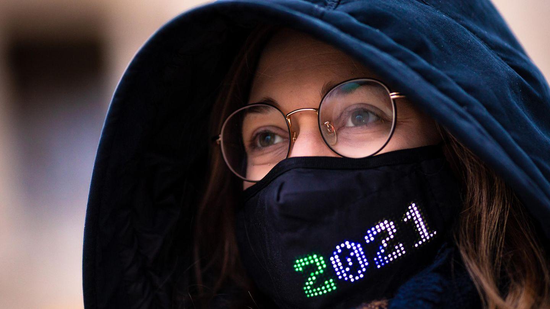 """Eine Frau mit Brille trägt eine dunkelblaue Kapuze sowie einen schwarzen Mund-Nasen-Schutz mit bunter """"2021""""-Stickerei"""