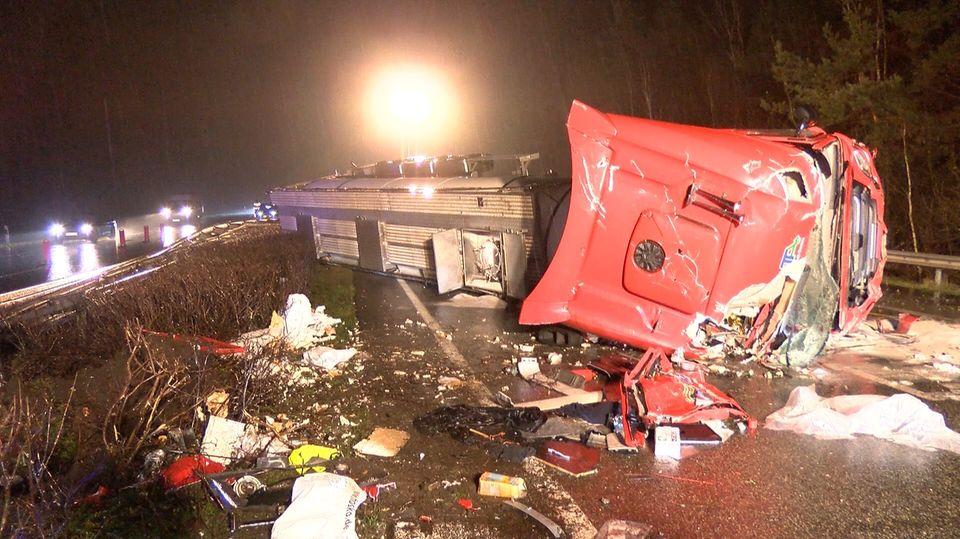 Ein Lkw liegt nach einem Unfall auf einer Autobahn auf der Seite und hat seine Ladung verloren