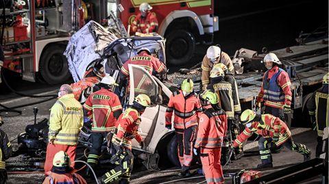 Rettungskräfte stehen um ein völlig zerstörtes Fahrzeug