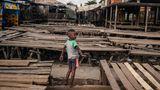 Ein Kind spielt in einem zerstörten Dorf in Madagaskar.