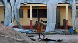 Eine Frau trägt ein Baby auf ihrem Rücken und geht an einer beschädigten Schule vorbei.