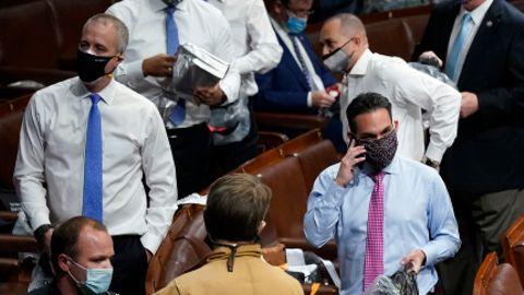 Abgeordnete bereiten sich darauf vor, Masken und Gasmasken im Repräsentantenhaus aufzusetzen, während Demonstranten das US-Kapitol betreten.