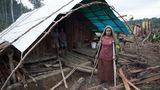 Eine verletzte Frau steht vor ihrer Holz-Hütte.