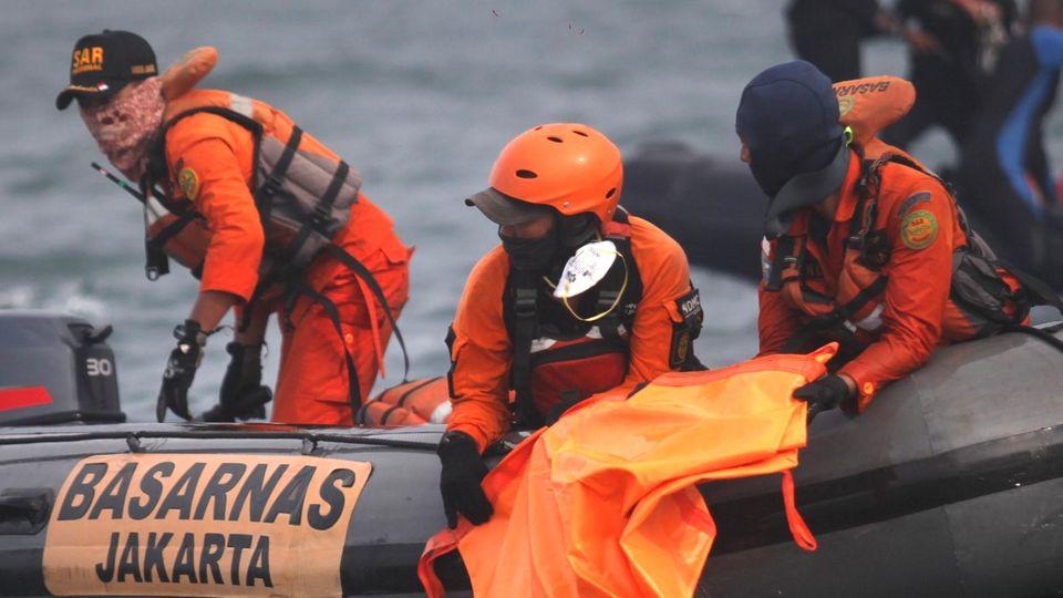 Von einem dunkelgrauen Schlauchboot aus halten drei Männer in orangen Overalls Ausschau über das Meer