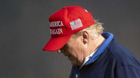 """Mit rotem """"Make America great again""""-Cap und blauem Pullover geht Donald Trump mit gesenktem Kopf über einen Golfplatz"""