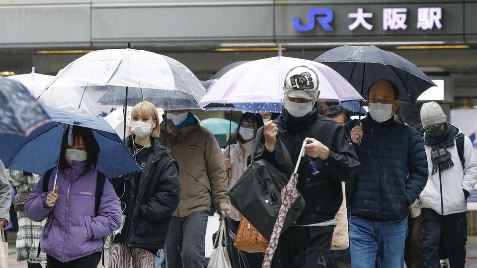 Menschen mit Mund-Nasen-Schutz gehen im Stadtteil Umeda in der Metropole Osaka über einen Fußgängerüberweg