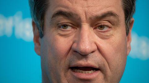 Vor einer weiß-blauen Wand ist das Gesicht von Bayerns Ministerpräsident Markus Söder in Großaufnahme zu sehen