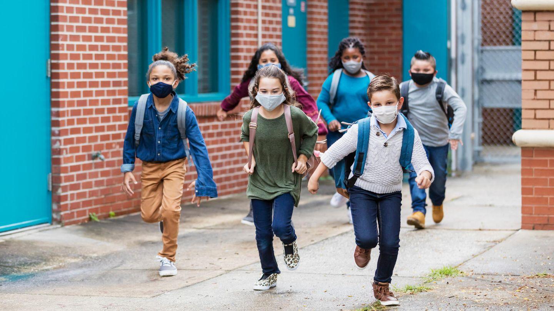 Grundschüler mit Masken rennen aus einer Schule