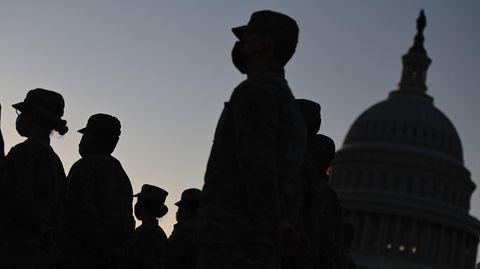 Im Gegenlicht sind Konturen von Uniformierten mit Käppis auf dem Kopf neben der Kuppel des US-Kapitols zu sehen