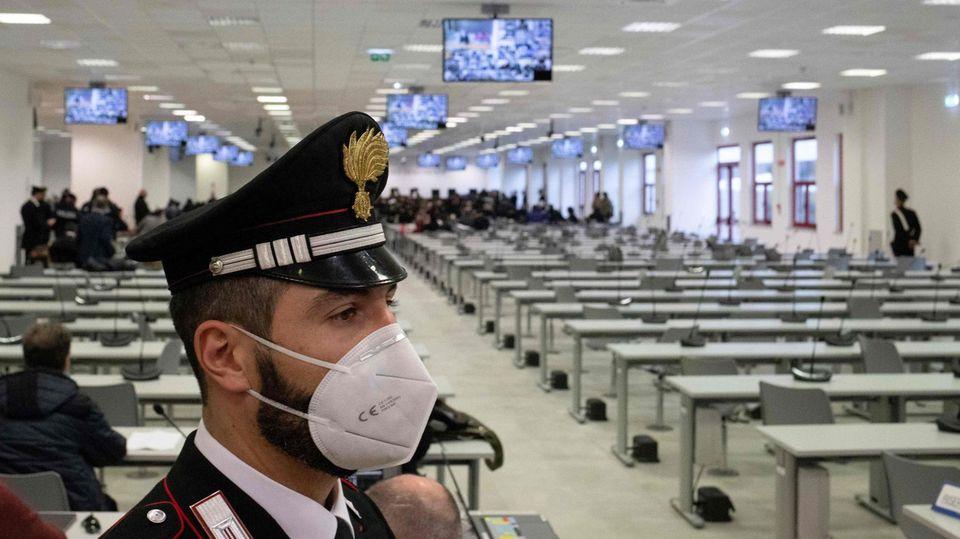 In einem riesigen Saal mit lauter Tischreihen mit Mikrofonen sowie Fernsehern an der Decke steht ein italienischer Polizist