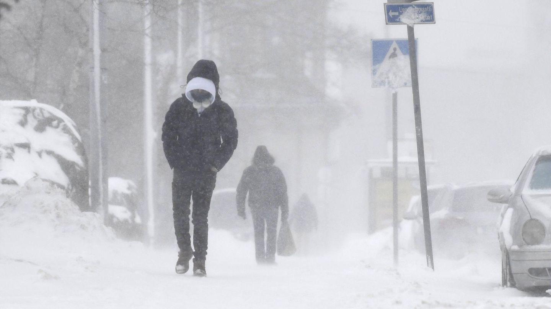 Zwei Passanten gehen in Helsinki über einen verschneiten Gehweg