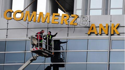Arbeiter demontieren den Commerzbank-Schriftzug an einer Filiale in Frankfurt