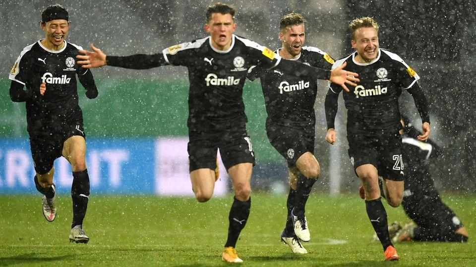 Spieler von Holstein Kiel laufen jubelnd auf die Kamera zu
