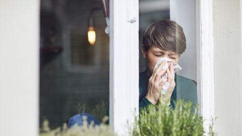 Frau putzt sich die Nase am Fenster