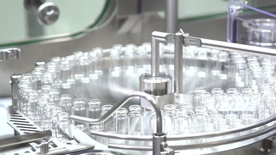 Auf einer runden Edelstahl-Abfüllanlage kreisen leere Ampullen für den Corona-Im pfstoff von Biontech
