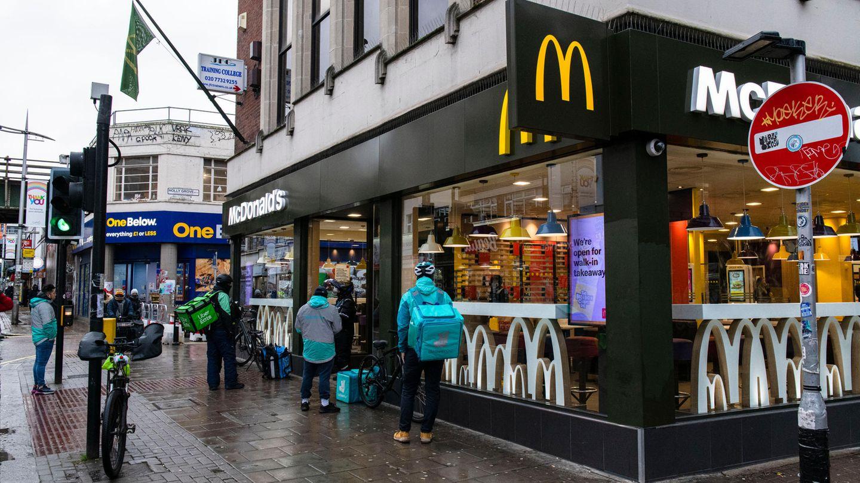 Eine Gruppe von Lieferfahrern wartet vor einem McDonalds in Peckham, Südlondon