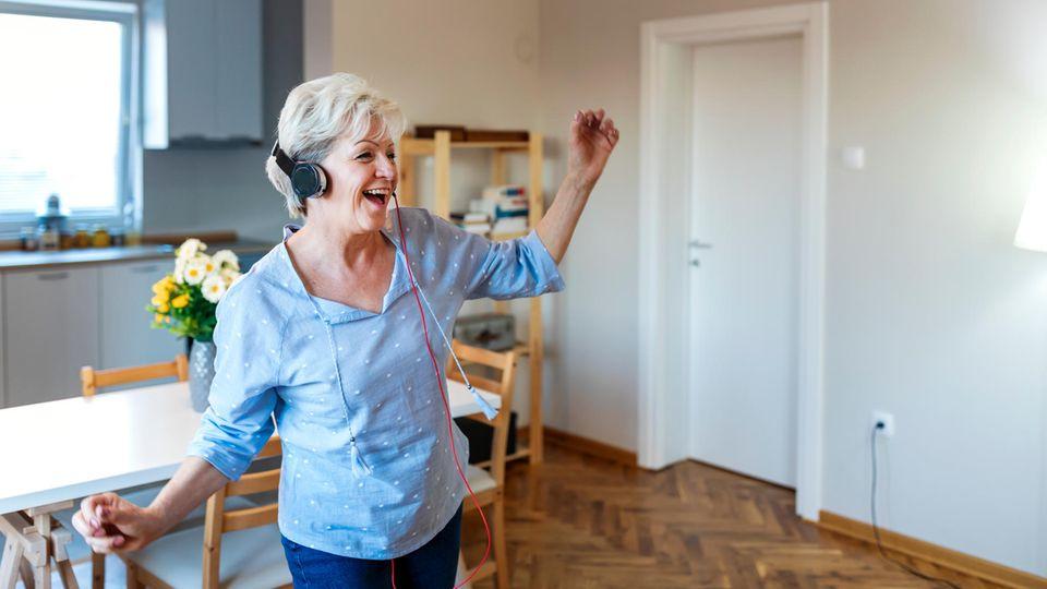 Frau mit Kopfhörern tanzt in Küche