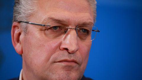 Ein Mann mit grau melierten Locken und randloser Brille schaut ernst. Im Hintergrund eine blaue Wand